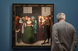 "© Licensed to London News Pictures. 06/07/2015. London, UK.  A visitor looks at Lucas Cranach the Elder's ""Boccal della Verità, the Mouth of Truth"" (est. £6m to £8m) at the preview of Old Masters, British Paintings and Masterworks from the collection of Castle Howard at Sotheby's ahead of the auction on July 8. Photo credit : Stephen Chung/LNP"