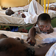 July, 15, 2006 - An HIV positive patient rests with his son by his beside at the district hospital in Rwinkwavu, Rwanda, which the Clinton Foundation renovated in partnership with Dr. Paul Farmer's Partners in Health. Photo by Evelyn Hockstein
