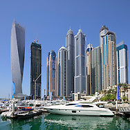 Dubai Marina with motor yacht and tall skyscraper residential apartment tower blocks