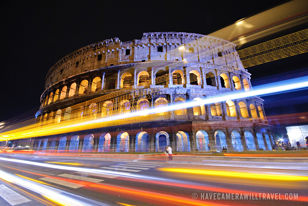 A night shot of Rome's famous and historic Coliseum, with lights of passing traffic streaking by in the foreground.