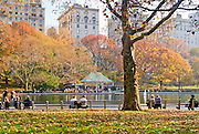 People sitting on benches around Conservatory Water in Central Park, New York City in Autumn with the Boathouse in background.