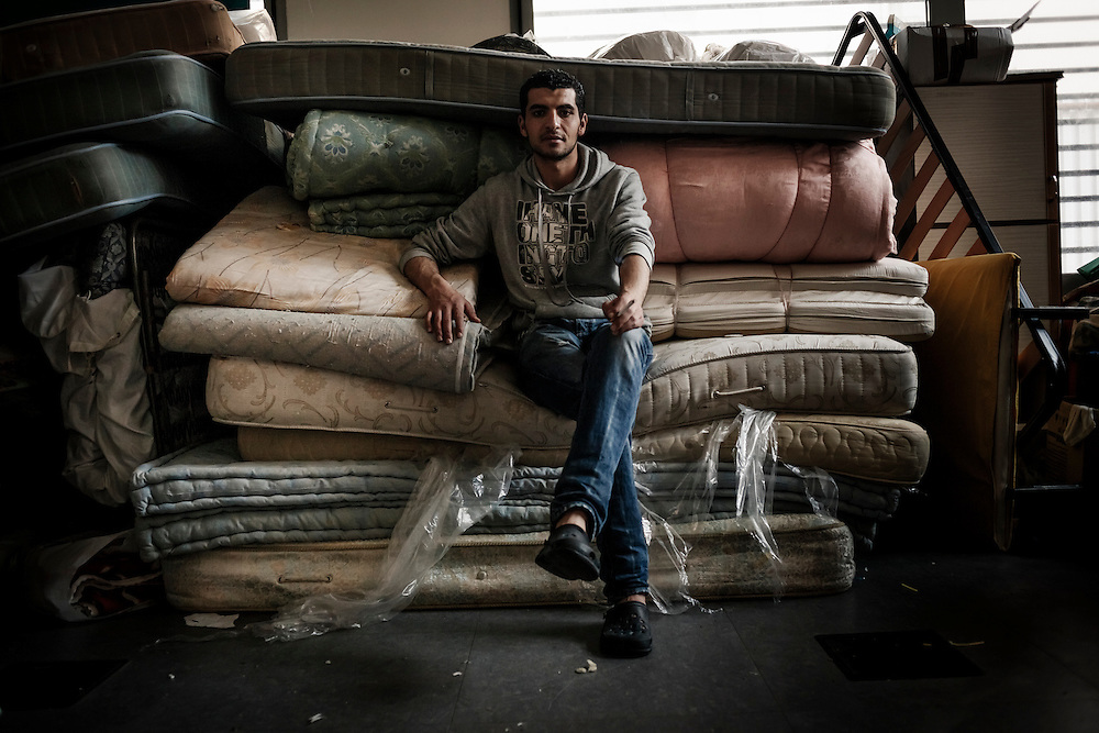 A refugee smokes a cigarette sitting on a stack of mattresses