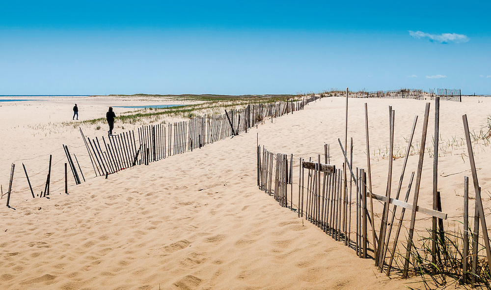 Two people walk on a sandy beach bordered by wood fences.9 Cape Cod, Massachusetts.