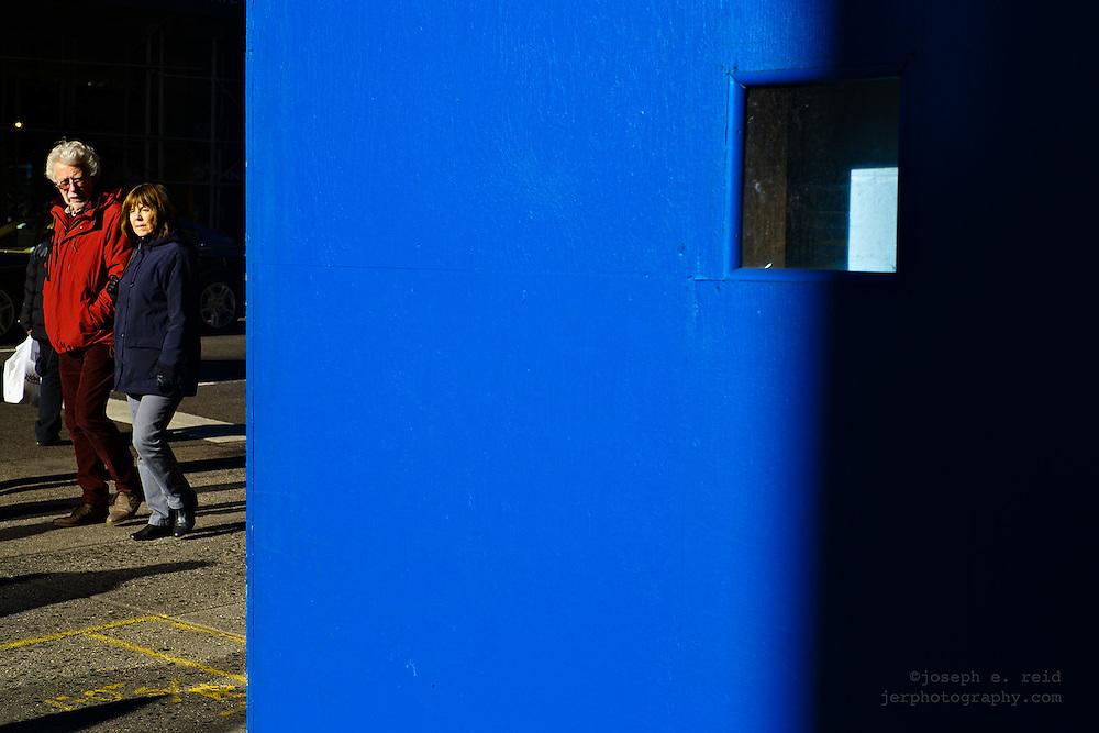 Pedestrians and blue wall