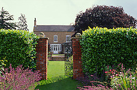 gateway through beech hedge leading across lawn to large house