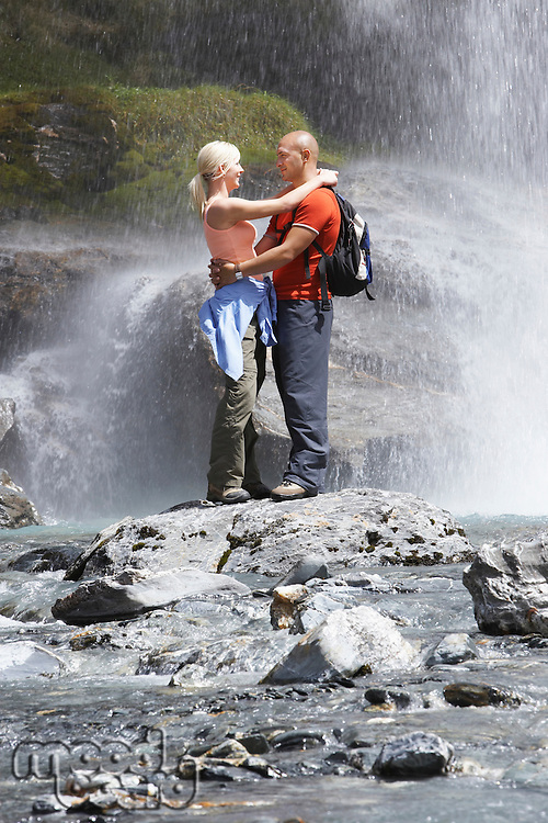 Couple embracing under spray of waterfall