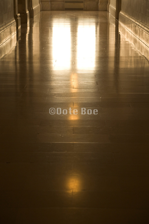light from light bulbs and from the window at the end of the hall reflecting on a shiny marble floor