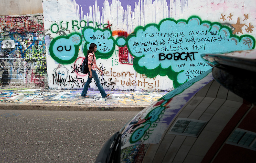 Kanola Azimous walks in front of the graffiti wall on West Mulberry Street in Athens, Ohio on July 5, 2012.