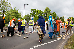 Slough, UK. 28th April 2019. Sikh women known as 'sewadars' sweep the path of the Vaisakhi Nagar Kirtan procession. Vaisakhi is the holiest day in the Sikh calendar, a harvest festival marking the creation of the community of initiated Sikhs known as the Khalsa.