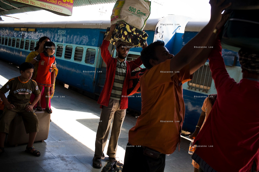 Porters assist with luggage as passengers disembark the Himsagar Express 6317 at Jammu Tawi station after its four day journey from Kanyakumari on 6th July 2009.. .6318 / Himsagar Express, India's longest single train journey, spanning over 3720 kms, going from the mountains (Hima) to the seas (Sagar), from Jammu and Kashmir state in the Indian Himalayas to Kanyakumari, the southern-most tip of India..Photo by Suzanne Lee / for The National.