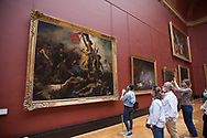 Small crowd watching Liberty lead the people of Delacroix at Louvre museum.