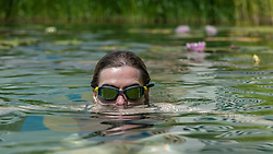 © Licensed to London News Pictures. 19/07/2016. London, UK. Evelyn, an office worker on her lunch break, enjoy the cooling waters of King's Cross pond on the hottest day of the year so far, with temperatures expected to reach 35C in the capital.  The UK's first ever man-made fresh water public bathing pond is a piece of innovative Land Art, within a working construction site area of London's King's Cross designed by Ooze architects. Photo credit : Stephen Chung/LNP