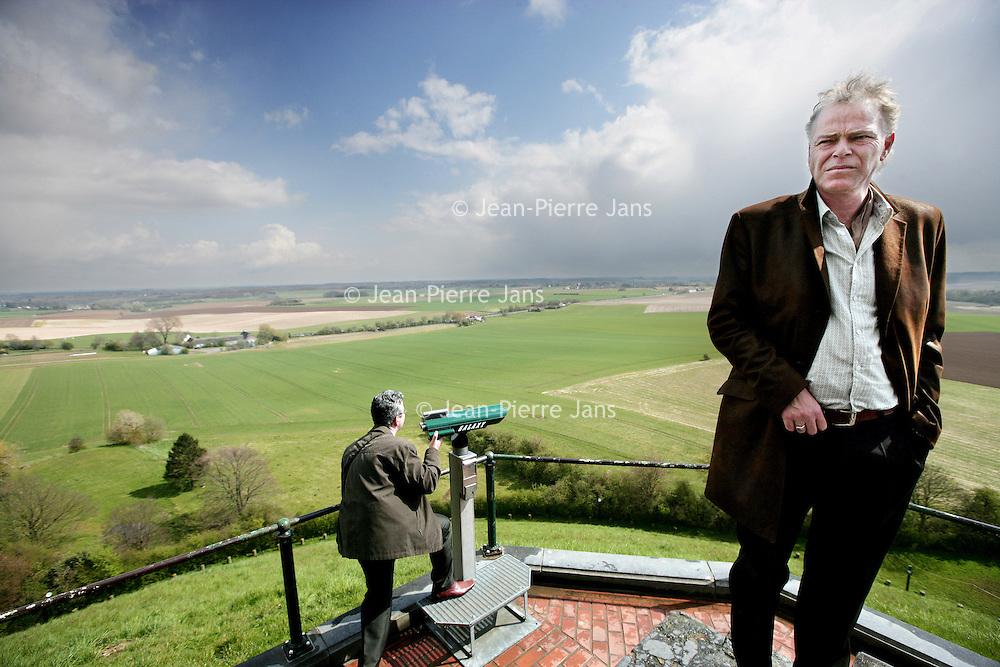 Belgie,Waterloo ,16 april 2008..Martin Bril (Utrecht, 21 oktober 1959) is een Nederlandse columnist en schrijver..Op de foto staat Martin bril op de kunstmatige heuvel met boven op de top De Leeuw van Waterloo (Butte du Lion)..De Leeuw van Waterloo  is een herdenkingsmonument voor de Slag van Waterloo (1815) en werd op bevel van koning Willem I van Nederland opgericht ter ere van zijn zoon, de prins van Oranje. Een reusachtige leeuw troont op een kunstmatige heuvel 45 meter boven de omringende vlakte uit. Het monument staat op het grondgebied van de gemeente Eigenbrakel.