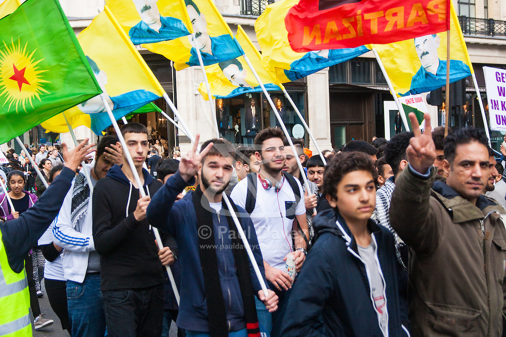 London, October 19th 2014. Hundreds of London's Kurdish community march throgh the capital in protest against ISIS and the Turkish government who they accuse, by not getting involved in military action against ISIS, of using the Jihadists to wipe out Kurds who have long been campaigning for an independent Kurdistan. PICTURED: The breeze catches the flags of protesters as they march on Regents Street.