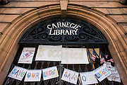 Protest banner and messages on the front gates of Carnegie Library in Herne Hill, south London while occupiers remain inside the premises on day 6 of its occupation, 5th April 2016. The angry local community in the south London borough have occupied their important resource for learning and social hub for the weekend. After a long campaign by locals, Lambeth have gone ahead and closed the library's doors for the last time because they say, cuts to their budget mean millions must be saved.