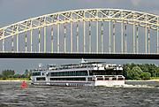 Nederland, Nijmegen, 16-8-2016Passagiers van een rijncruise genieten op het zonnedek van hun schip van het mooie weer. Het schip vaart juist onder de Waalbrug door.Foto: Flip Franssen