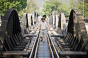"20 FEBRUARY 2008 -- KANCHANABURI, THAILAND: Tourists on the ""Bridge over the River Kwai"" in Kanchanaburi, Thailand. The infamous bridge and the ""Death Railway"" that connected Thailand and Burma were built by Japanese military forces using prisoner of war and slave labor during World War II. More than 200,000 POWs and laborers were used to build the railway, about half of them died during the construction.  Photo by Jack Kurtz"