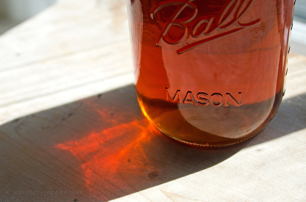 Sunlight casts amber patterns as it filters through a glass mason jar full of organic maple syrup made in Bar Harbor, Maine.