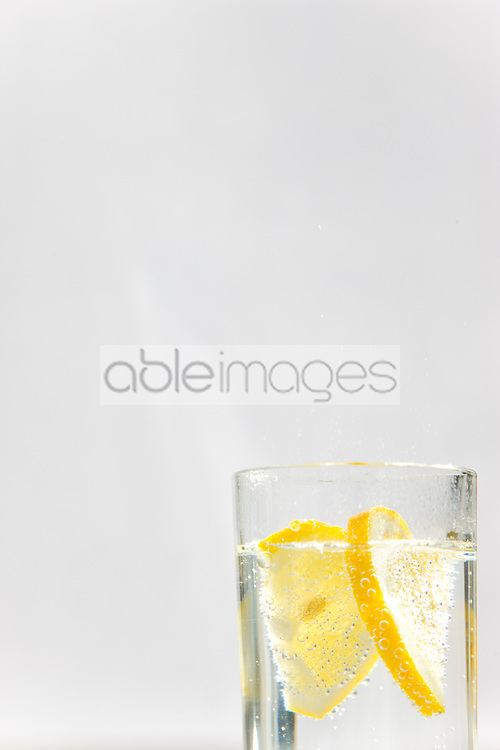 Close up of a glass of sparkling water and sliced lemon