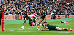 England's Jermaine McGillvary (left) scores the opening try of the game against Australia during the Four Nations match at London Stadium.