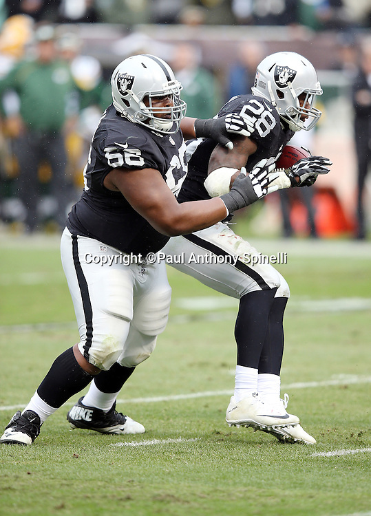 Oakland Raiders running back Latavius Murray (28) runs into Oakland Raiders guard Gabe Jackson (66) as he runs the ball in the first quarter during the 2015 week 15 regular season NFL football game against the Green Bay Packers on Sunday, Dec. 20, 2015 in Oakland, Calif. The Packers won the game 30-20. (©Paul Anthony Spinelli)