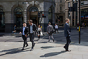 Strangers to and fro in a sunny City of a London street corner.