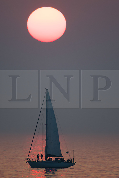 © Licensed to London News Pictures. 29/05/2018. Aberystwyth, UK. The Bank Holiday Monday comes to a close with a spectacular orange sunset over a yacht floating ion the flat calm waters of Cardigan Bay, just off the beach at Aberystwyth on the west coast  of Wales .Photo credit: Keith Morris/LNP