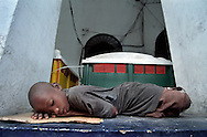 An orphan boy sleeps in the window of a police station in Port-au-Prince, Haiti, May 1995. (Photo by Roger M. Richards)