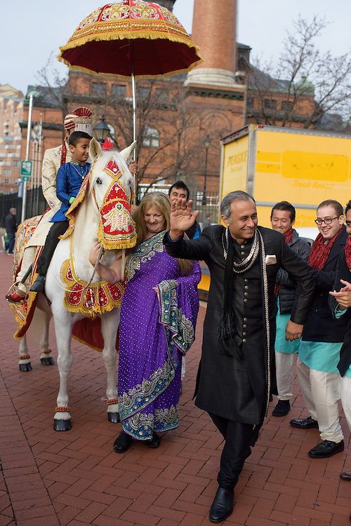 Baltimore, Maryland - December 20, 2014: Eshwan Ramudu rides Chico, a male 22 year-old, Andalusian horse, from Mt. Airy, MD outside the Baltimore Marriott Waterfront Hotel for his baraat. Riding with Eshwan is his bride's nephew Arjun Khanna. By tradition, a young boy, the &quot;sarbala&quot; from the family who rides the with the groom as protection from others who might wish ill upon him. Eshan's future father in law Pankaj Pasricha dances in the foreground. <br /> <br /> Trisha Satya Pasricha and Eshwan Ramudu married at the Baltimore Marriott Waterfront Hotel December 20, 2014. <br /> <br /> <br /> CREDIT: Matt Roth for The New York Times<br /> Assignment ID: 30168620A