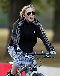 A low rider Madonna out cycling in London with two personal trainers. The Material Girl singer, 58, wearing Alexander Wang/Adidas Originals top, check trousers which were half way down showing off her perk derrière and underwear was spotted riding around Hyde Park. UK. 13/09/2016 <br />