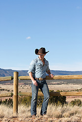 cowboy leaning against a wooden split rail fence on a ranch overlooking a mountain range