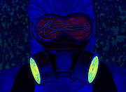 Portrait of a person wearing Haz Mat coveralls and an air filter with the Ebola virus reflected in his goggles.Black light