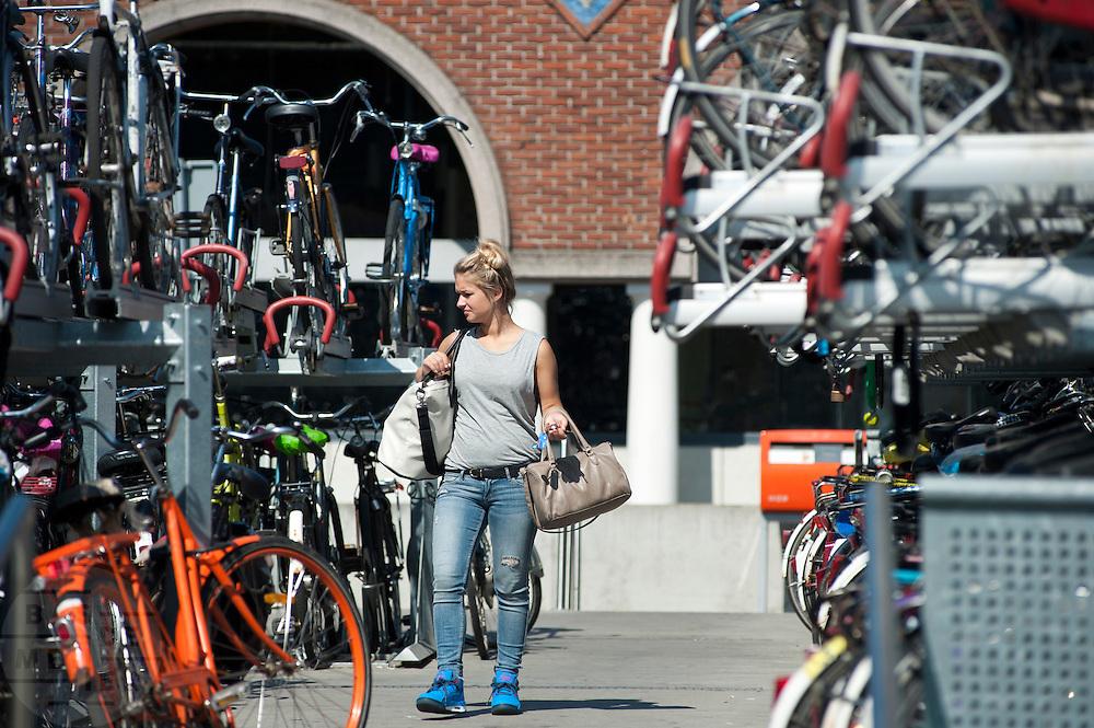 In Nijmegen zoekt een meisje naar haar fiets in de volle fietsenstalling bij het station.<br /> <br /> In Nijmegen a girl is looking for her bike at the crowded bike parking near the train station.