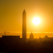 The rising sun silhouettes the Lincoln Memorial, Washington Monument, and US Capitol Dome on Washington DC's National Mall.