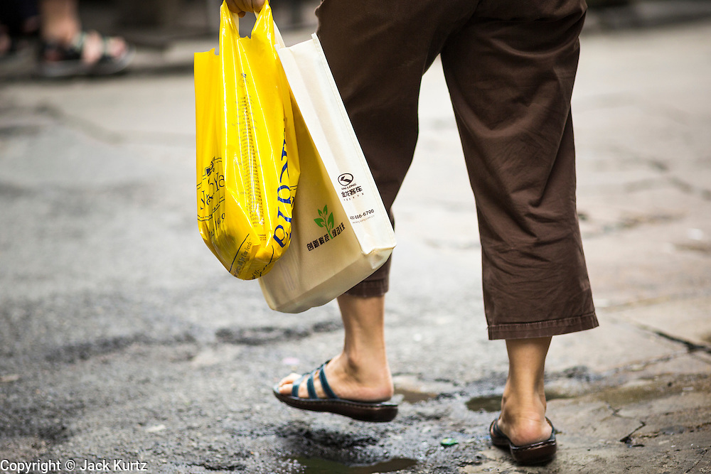 """24 AUGUST 2013 - BANGKOK, THAILAND: A woman carries her shopping bags home along Sukhumvit Road in Bangkok. Thailand entered a """"technical"""" recession this month after the economy shrank by 0.3% in the second quarter of the year. The 0.3% contraction in gross domestic product between April and June followed a previous fall of 1.7% during the first quarter of 2013. The contraction is being blamed on a drop in demand for exports, a drop in domestic demand and a loss of consumer confidence. At the same time, the value of the Thai Baht against the US Dollar has dropped significantly, from a high of about 28Baht to $1 in April to 32THB to 1USD in August.     PHOTO BY JACK KURTZ"""