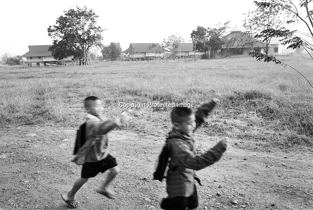 Auf dem Weg zur Schule spielen YOK, 8 Jahre alt, 1v.r. und BOM, 7 Jahre alt, 2v.r., ihre eigenen Spielchen. Im Hintergrund sind die Haeuser aus dem Dorf BAAN GERDA, zu sehen..Beide Jungen sind HIV-positive Waisenkinder und haben sich hier kennengelernt. Ihnen geht es durch die Behandlung mit AIDS-Medizin und der Fuersorge in BAAN GERDA viel besser. Sie sind aeusserlich von gesunden Kinder nicht zu unterscheiden. Provinz Lop Buri, Thailand..YOK, age 8, at right, and BOM at left, playing games on their way to the school. They become  good friends, after they arrived in BAAN GERDA. Fournatly the get much better since they be taken care with Aids-medicine and in their new families..At the background the houses of BAAN GERDA. .Lop Buri, Thailand.....