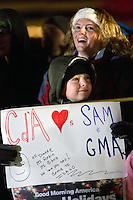 """JEROME A. POLLOS/Press..Nate Sakwi and his mother Genca Sakwi stand alongside the parade route just before 4 a.m. in hopes of attracting a cameraman to their sign expressing Coeur d'Alene's love for weather anchor Sam Champion and the """"Good Morning America"""" show."""