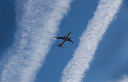 """© Licensed to London News Pictures. 27/10/2016. London, UK. An airliner takes off from Heathrow between aircraft vapour trails. The government has announced that a third runway will be built at the United Kingdom's busiest airport. The Cabinet are divided - with Foreign Secretary Boris Johnson saying that the project is """"undeliverable"""". Conservative MP for Richmond Zac Goldsmith has resigned. Photo credit: Peter Macdiarmid/LNP"""