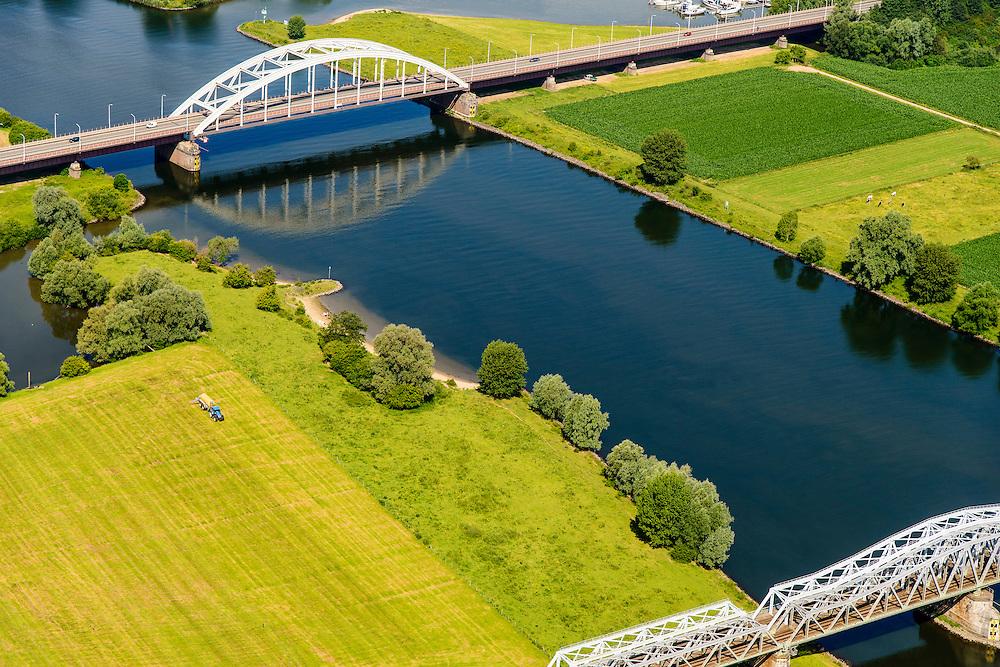 Nederland, Noord Brabant, Gemeente Den Bosch, 26-06-2014. Dubbele spoorbrug over de Maas, ter hoogte van Hedel. Hedelse spoorbrug (dubbelspoor). De boogbrug in de achtergrond is de Hedelse brug met de Oude Rijksweg.<br /> Double track railway bridge and <br /> arch bridge over the Meuse, near Hedel.<br /> luchtfoto (toeslag op standaard tarieven);<br /> aerial photo (additional fee required);<br /> copyright foto/photo Siebe Swart.