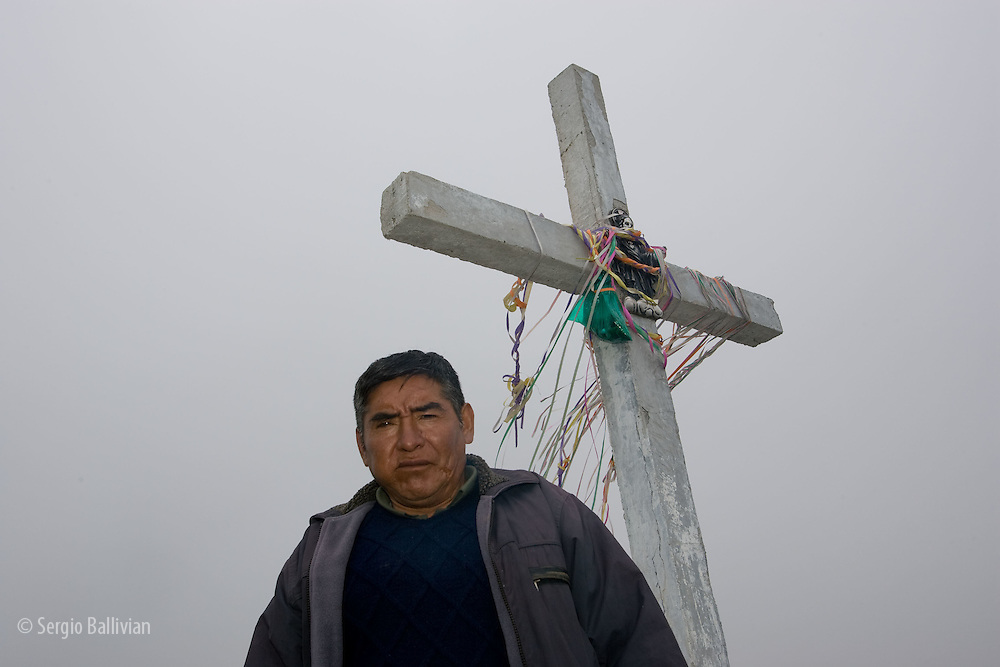 "A Kallawaya spiritual man performs a ""ch'alla"" to appease the spirits at the ""Cumbre"" pass near La Paz, Bolivia"