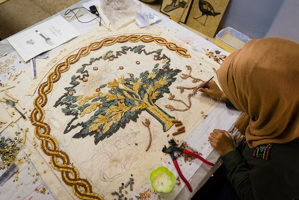 A female student at the Institute for Mosaic Art and Restoration in Madaba, Jordan, creates a mosaic based on a drawing on textile. Photo © Robert van Sluis