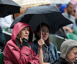 LONDON, ENGLAND - Monday, June 20, 2011: Spectators shelter from the rain on Centre Court during the Ladies' Singles 1st Round match on day one of the Wimbledon Lawn Tennis Championships at the All England Lawn Tennis and Croquet Club. (Pic by David Rawcliffe/Propaganda)