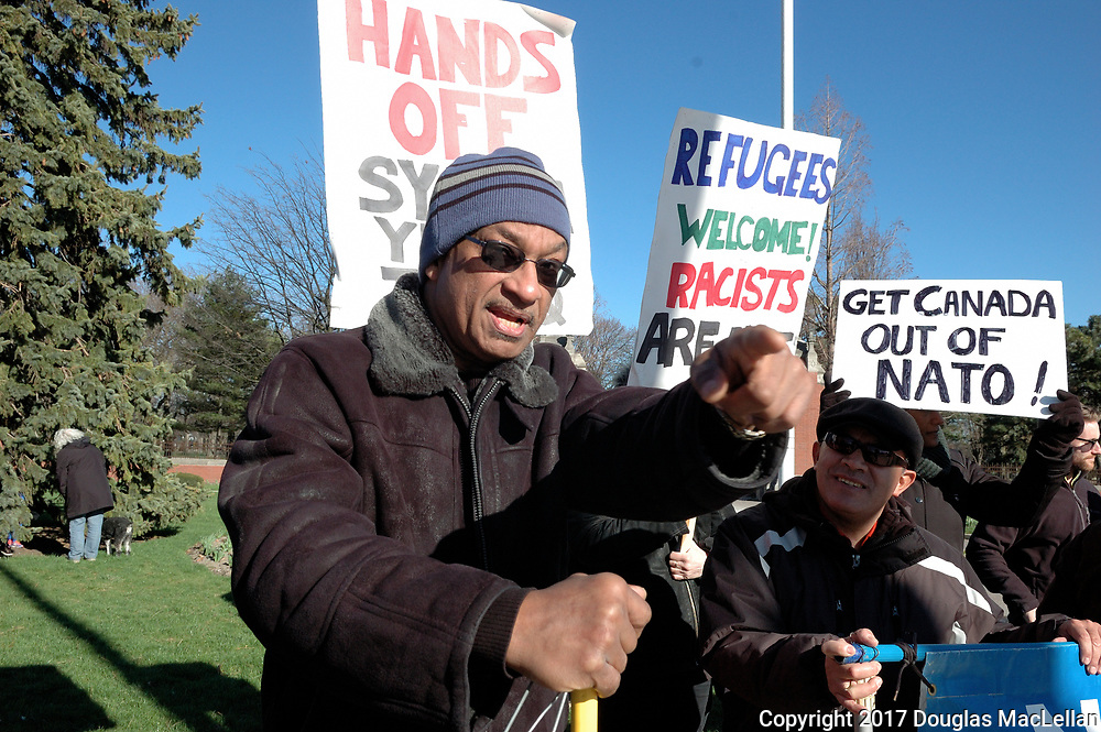 CANADA, Windsor. 07 April 2017. Windsor Peace Coalition holds a demonstration against yesterday's United States bombing of a Syrian air force base. About twenty people, mostly older, gather at Jackson Park during the afternoon rush hour. There is also a counter demonstration by two men holding a Trump banner on the same street corner. NOTE: Agefotostock exclusive image, G99-2864934, to license go to http://www.agefotostock.com/age/en/Stock-Images/Rights-Managed/G99-2864934