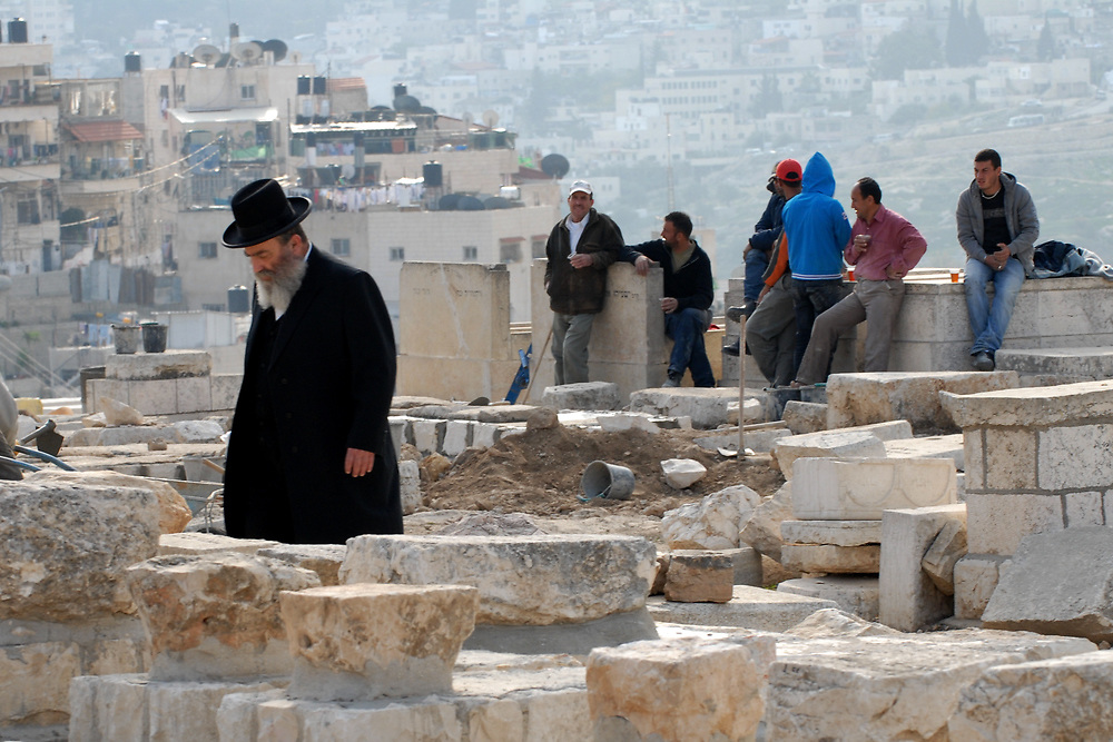 An ultra orthodox Jewish man walks next to Palestinian workers in the Jewish graveyard on mount of olives in Jerusalem's old city in December 10, 2009. Photo by Gili Yaari