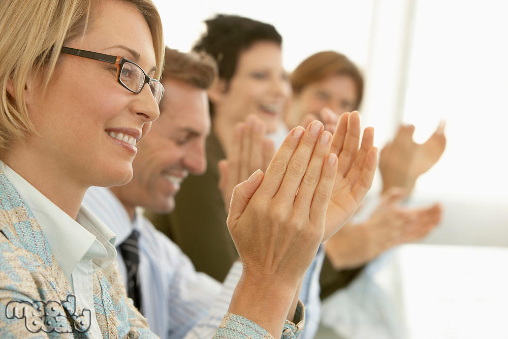 Businesspeople clapping in conference meeting