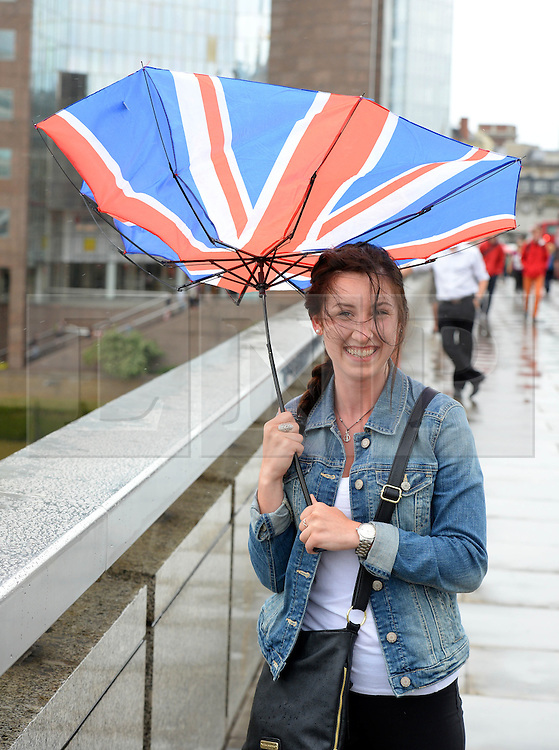 © Licensed to London News Pictures. 14/06/2014. London, England. A young lady struggles with her umbrella on London Bridge during a lunchtime rain shower. Photo credit : Mike King/LNP