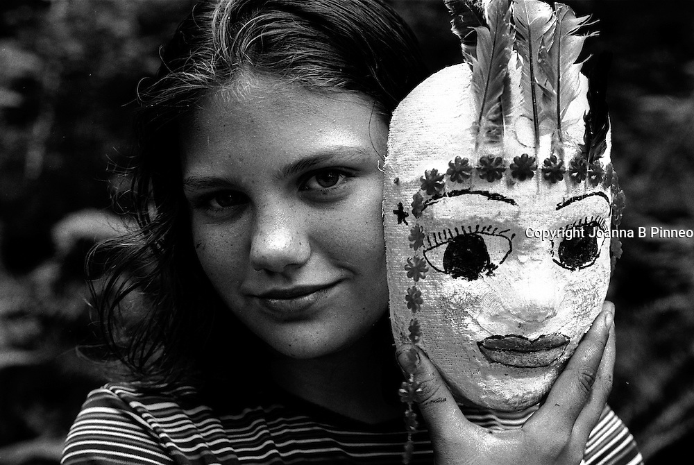 Joanna B. Pinneo All Rights Reserved.Olympic Peninsula. Cary Amell, age 11, poses with her childhood mask.  She is on a Wilderness Coming of Age Journey organized by the Institute of Cultural Affairs  out of Bothell, Washington. Girls age 11-13 take a 3-week backpacking trip in the heart of the Olympic Peninsula and then participate in a 24-hour solo journey while camping out on the beach.