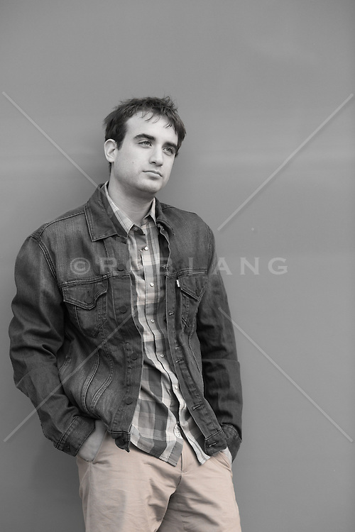 man leaning against a wall with an aloof expression