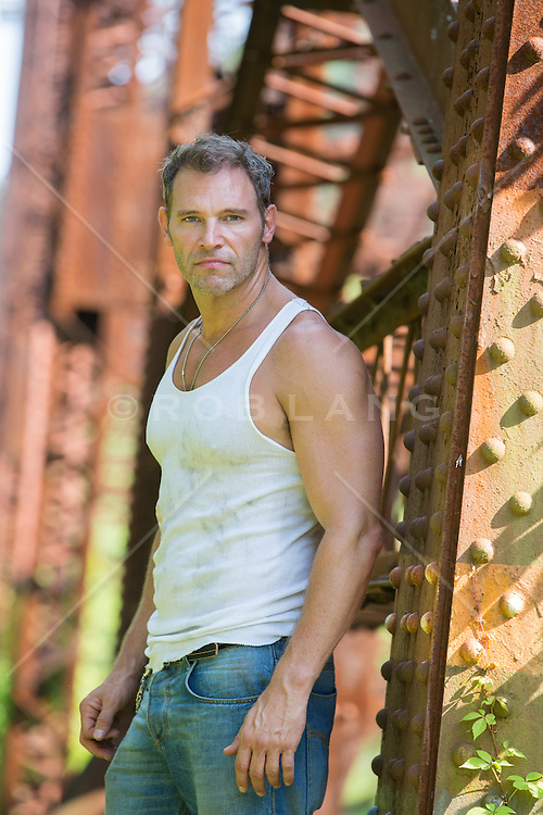middle aged man in a tank top on a railroad trestle,