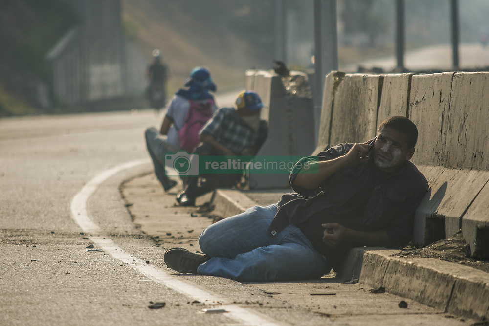 April 30, 2019 - Caracas, Miranda, Venezuela - Protesters seen getting down low on the ground to avoid bullets. .Venezuelan military who are supporting the Venezuelan opposition leader Juan Guaido took to the street with their weapons together with anti government protesters in a military coup against the socialist government lead by President Nicolas Maduro. (Credit Image: © Roman Camacho/SOPA Images via ZUMA Wire)